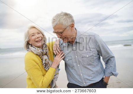 Portrait of happy modern senior couple on beach in fall
