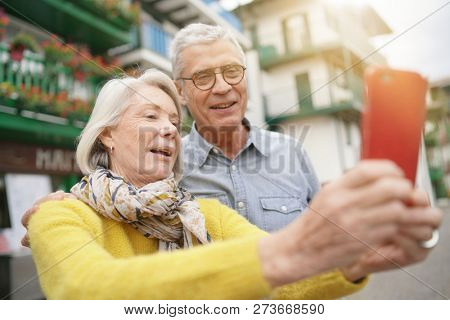 Attractive senior couple taking a selfie outdoors