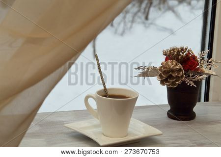 Exclusive Porcelain Cup With Black Tart Aromatic Coffee And Decorative Bouquet In Ceramic Vase On A
