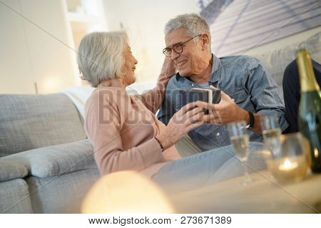 Modern senior couple exchanging gifts at home