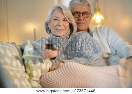Senior couple at home relaxing on couch watching TV and looking at tablet