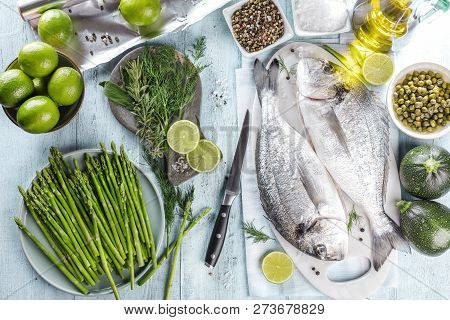 Fresh Raw Sea Bream Fish Cooking On Black Stone Countertop, Top View.