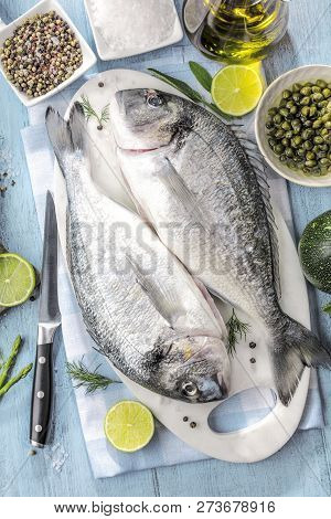 Fresh Raw Sea Bream Fish Cooking On Black Stone Countertop, Top View