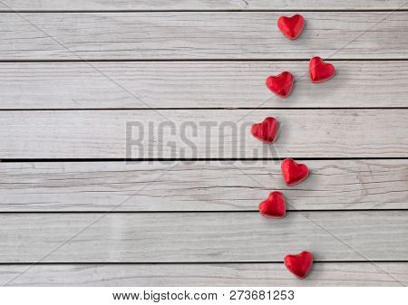 valentines day, sweets and confectionery concept - close up of red heart shaped chocolate candies over grey wooden boards background