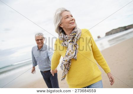 Vibrant senior woman holding husband's hand and leading the way on beach walk