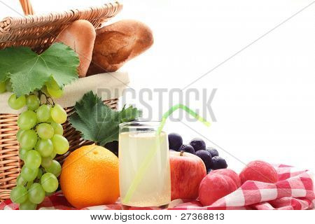 Picnic basket with fruits  and a glass of  lemon juice on white background.