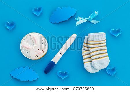 Pregnancy and preparation for childbirth. Babyshower. Pregnancy test near socks and hearts blue background top view poster