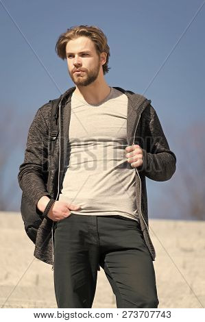 Man With Beard In Casual Wear On Sunny Outdoor, Fashion. Macho Stand On Blue Sky, Perspective. Persp