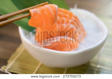 Chopsticks With Salmon Sashimi With Salmon Sashimi On Ice In With Bowl. Japanese Food In Asian Restu