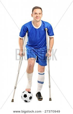 Full length portrait of an injured soccer football player on crutches isolated on white background