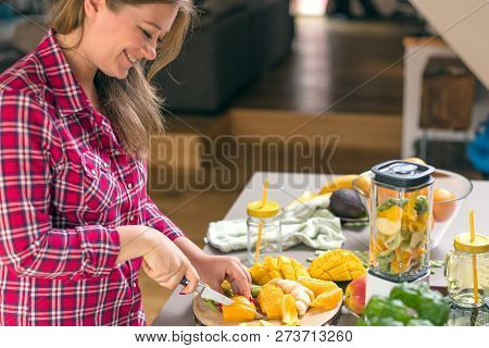 Young Smiling Woman Making Smoothie With Fresh Greens In The Blender In Kitchen At Home