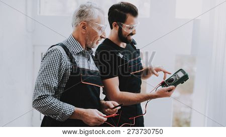 Workers Checking Device In Hands In Repair Shop. Worker With Tools. Computer Hardware. Young And Old