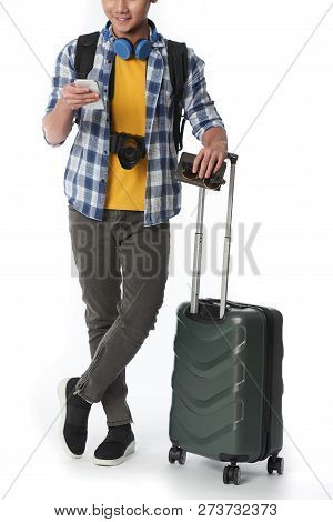 Smilng Man With Luggage And Passport Checking Schedule On His Phone