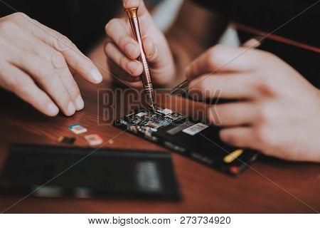 Close Up. Men Repairing Hardware Equipment In Workshop. Repair Shop. Young And Old Workers. Digital