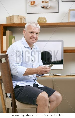 Senior Mature Project Manager With Smartphone Sitting At Office Table