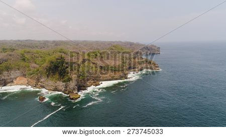 Aerial View Rocky Coastline With Cliffs, Ocean Surf With Breaking Waves In Coast. Seascape Waves Bre