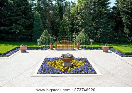Sunny Day In A Spring Garden With Wooden Bench, Clay Pots And Blossoming Flowers- Concept Of Lifesty