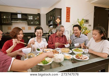 Group Of Cheerful Asian People Enjoying Good Food At Table Served For Tet, Couplets With Best Wishes