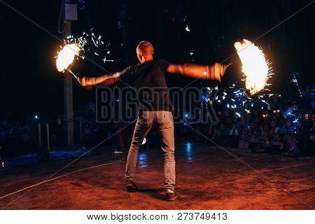Vichuga, Russia - June 17, 2018: Fire Show, A Man Fakir Waving Burning Torches