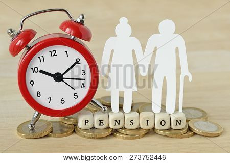 The Word Pension Written With Wooden Blocks, Paper Elderly Couple And Alarm Clock On Coins - Pension
