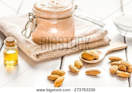 Natural Scrub With Almond Oil And Sugar On Light Table Backgroun