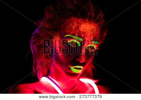 Portrait of a beautiful young sexy girl in neon lent with ultraviolet paint on her body. Pretty woman with glowing bodyart in black lamp light poster