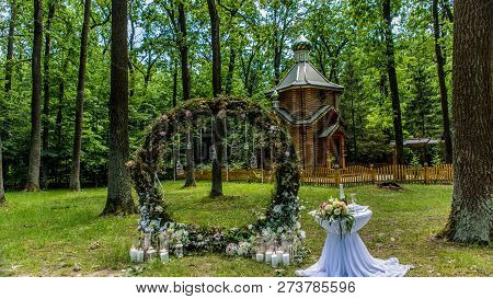 Arch For The Wedding Ceremony. Decorated With Fabric Flowers And Greenery. Is Located In A Pine Fore