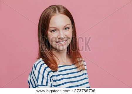 Sideways Shot Of Pleasant Looking Happy Brown Haired Woman With Straight Hair, Healthy Skin, Pleasan
