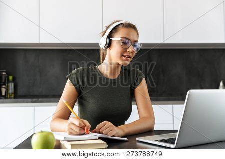 Smiling young woman sitting at the kitchen, using laptop computer for study, listening to music with headphones