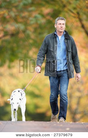 Man Walking Dog Through Autumn Park Listening to MP3 Player