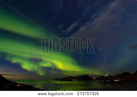 Northern Lights Dancing Over A Fjord Reflected In The Sea