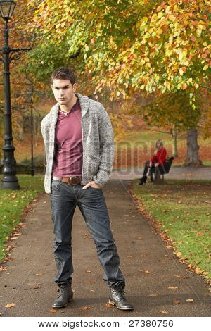 Teenage Boy Standing In Autumn Park With Female Figure On Bench In Background