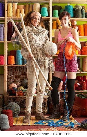 2 Women Wearing Knitted Scarf Standing In Front Of Yarn Display Holding Giant Needles