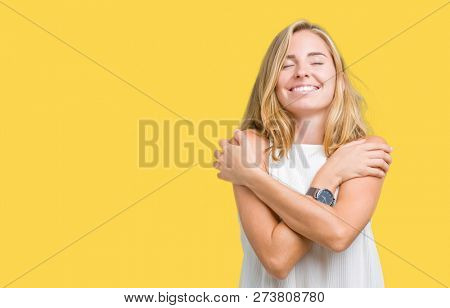 Beautiful young elegant woman over isolated background Hugging oneself happy and positive, smiling confident. Self love and self care