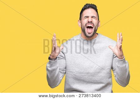 Young handsome man wearing sweatshirt over isolated background crazy and mad shouting and yelling with aggressive expression and arms raised. Frustration concept.
