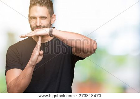 Young handsome man over isolated background Doing time out gesture with hands, frustrated and serious face