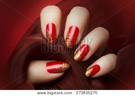 Female Hand With Beautiful Red And Golden Glittered Nails Is Holding A Dark Red Textile On Red Backg