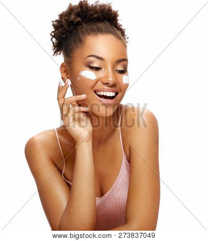 Laughing Woman With Moisturizing Cream On Her Face. Photo Of African American Woman With Flawless Sk