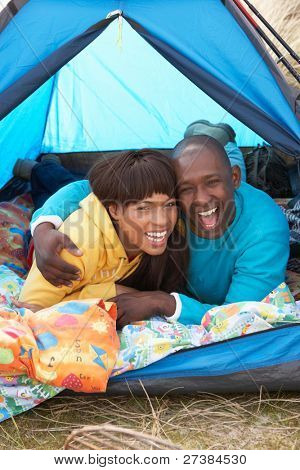 Young Couple Relaxing Inside Tent On Camping Holiday