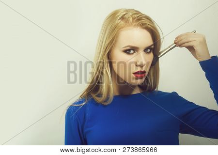 Woman Applying Powder On Face Skin With Makeup Brush. Pretty Girl With Blond Long Hair Wearing Blue