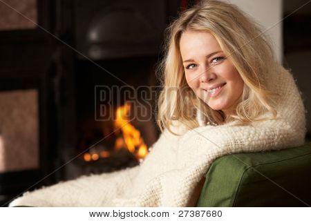 Junge Frau sitzen am offenen Feuer