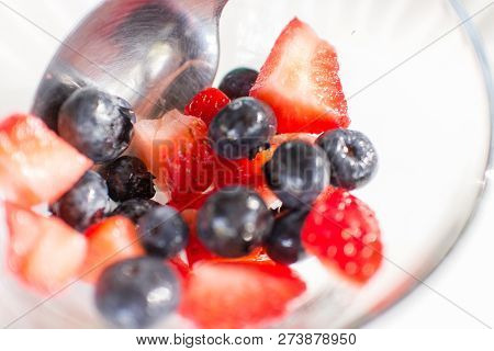 Blueberries & Strawberries In A Small Glass Bowl With A Spoon.