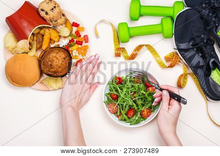 Young Woman Refuses To Eat Junk Food And Makes Choice To Do Exercises And Eat Healthy Meal. Preparin