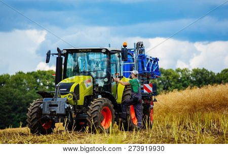 Vinnitsa, Ukraine - July 2017: A Young Farmer On Farmland With A Tractor. Agricultural Field With Cr