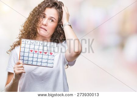 Young brunette girl holding menstruation calendar over isolated background stressed with hand on head, shocked with shame and surprise face, angry and frustrated. Fear and upset for mistake.