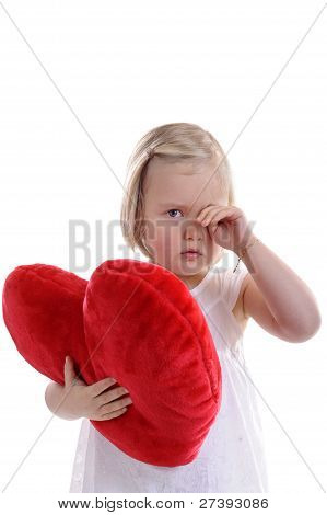 Tired Little Girl With Red Heart Shaped Pillow Rubbing Her Eyes