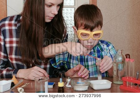 Chemistry Experiments At Home. Mom And Son Make A Chemical Reaction With The Release Of Gas In The T