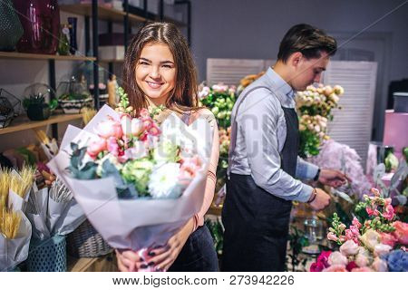 Cheerful Young Female Florist Look On Camera And Smile. She Hold Bouquet Of Flowers In Hands. Male F