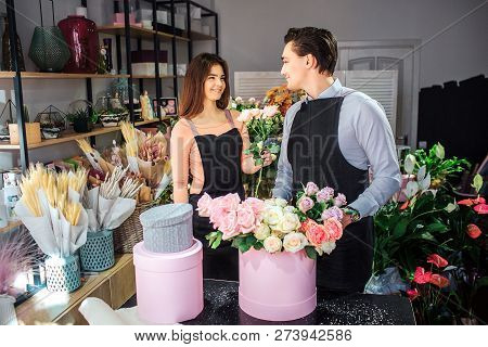 Cheerful And Nice Young Florists Stand In Room And Look At Each Other. They Smile. Female Florist Ho