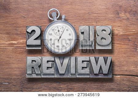 2018 Review Phrase Combined On Vintage Varnished Wooden Surface With Stopwatch Inside